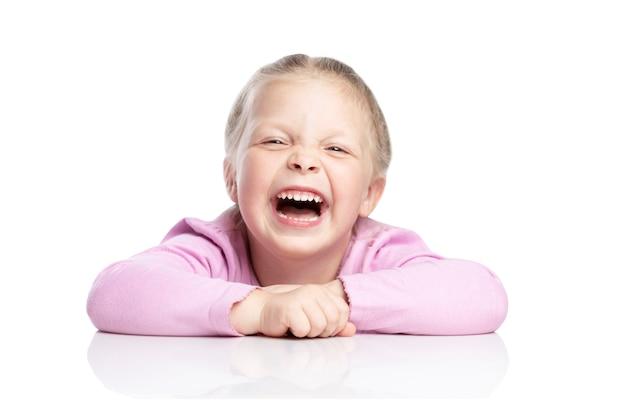 Kleine blonde meisje in een roze trui lacht. geã¯soleerd op witte achtergrond.