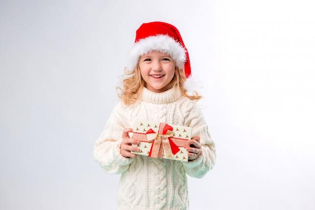Kleine blonde meisje in kerst muts houden geschenkdoos