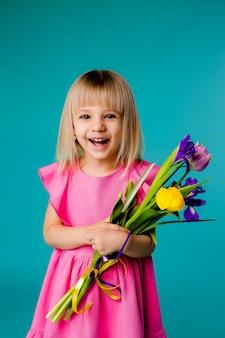 Kleine blonde meisje lacht in een roze jurk en met een boeket van lentebloemen op een blauwe ruimte isoleren