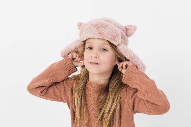 Kleine blonde meisje speelt met haar oren