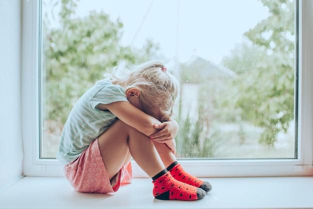 Kleine blonde meisje zit op de vloer omhelst haar knieën, in de buurt van venster thuis, haar hoofd naar beneden, verveeld, verontrust met ouders vechten