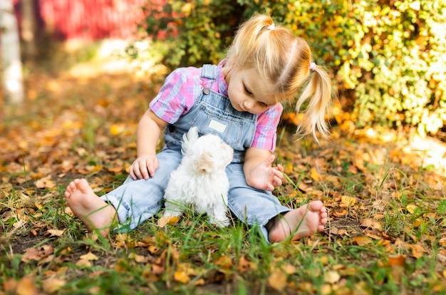Kleine blonde peuter meisje met twee vlechten spelen met mooie witte puppy