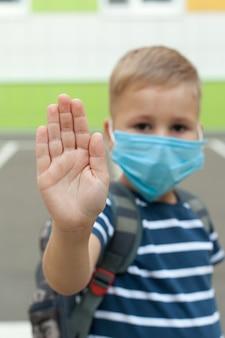 Kleine blonde schooljongen die masker draagt tijdens de uitbraak van het coronavirus
