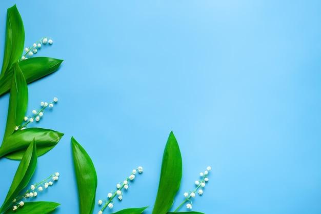 Kleine boeketten van lelietje-van-dalen als een bloemenkader aan de linkerkant met kopieerruimte plat gelegd met b ...