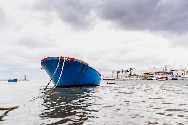 Kleine boot afgemeerd aan de haven van bari, italië, tijdens een storm op zee.