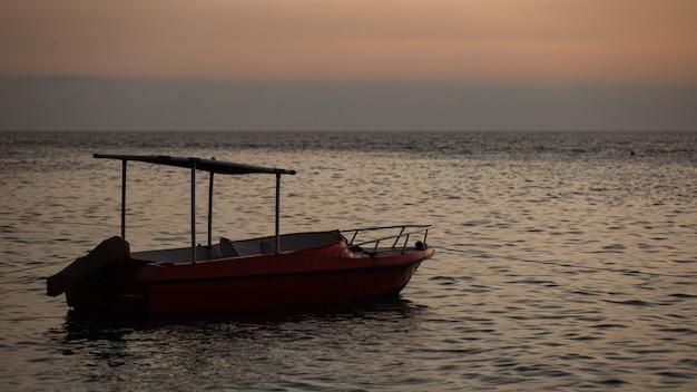 Kleine boot drijft op het water met bergen.