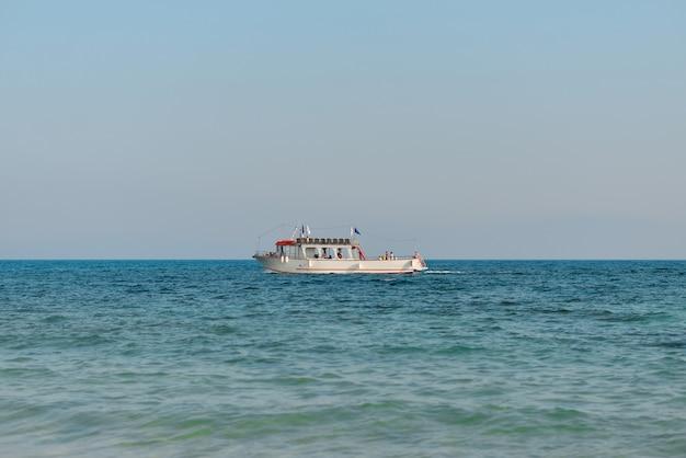 Kleine boot in het midden van de zee op een heldere hemel.