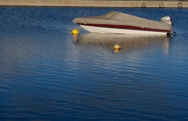 Kleine boot of jacht afgemeerd in het midden van het kalme water van een meer of zee nabij het dok