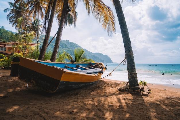 Kleine boot op de zandige kust aan zee, gevangen op een zonnige dag