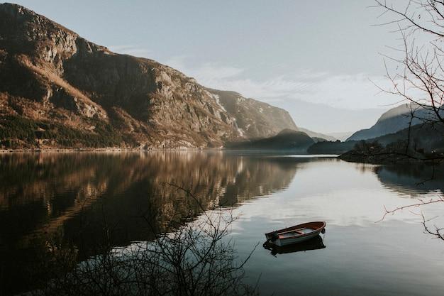 Kleine boot op stilstaand water in fjaerland, noorwegen