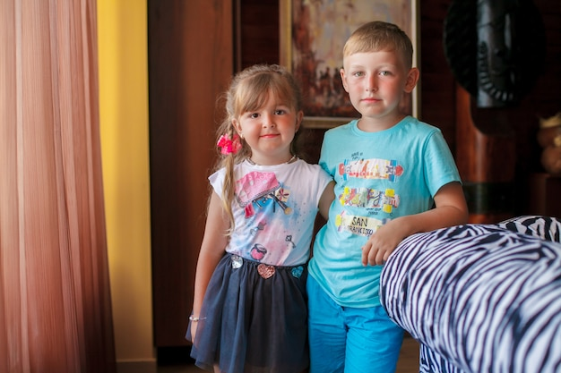 Kleine broer en zijn zus staan voor het raam.