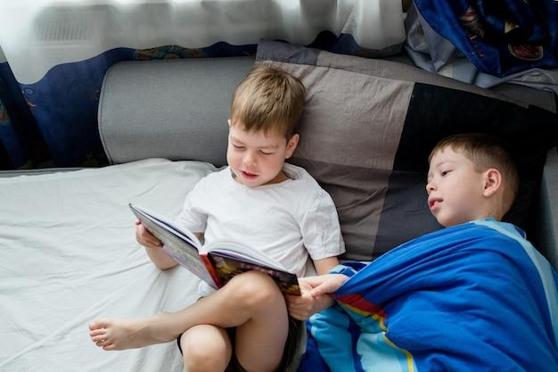 Kleine broer leest een boek op het bed voor een ouderling. vriendschap tussen broers. liefde voor lezen. leeuwerik en uil onder de mensen. 2 jongens op het bed lezen een boek. slaap verhaaltjes