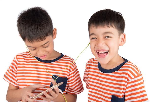 Kleine broer of zus jongen spelen spel op mobiel samen