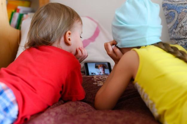 Kleine broers en zussen communiceren via videochat met hun grootmoeder