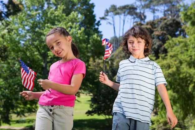 Kleine broers en zussen die amerikaanse vlag golven