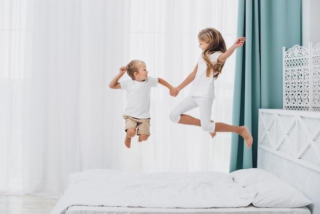 Kleine broers en zussen springen in bed