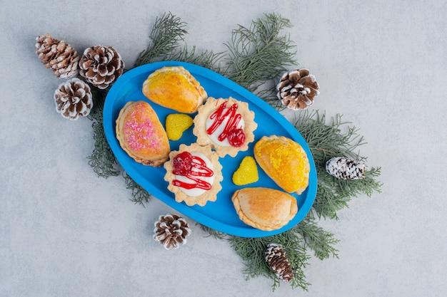 Kleine broodjes, cupcakes en geleisuikergoed op een blauwe schotel versierd met dennenbladeren en kegels op marmeren oppervlak