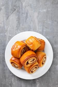 Kleine broodjes met kaneel op witte plaat op ceramische achtergrond