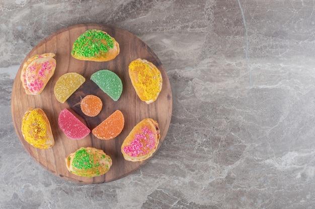 Kleine broodjes met verschillende toppings en gelei-snoepjes op een bord op een marmeren oppervlak