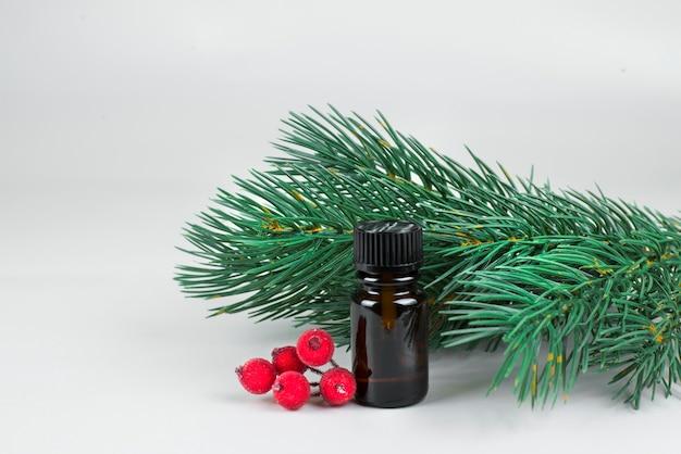 Kleine bruine cosmetische fles met kerstboomtakken en rode kerstspullen op lichte achtergrond