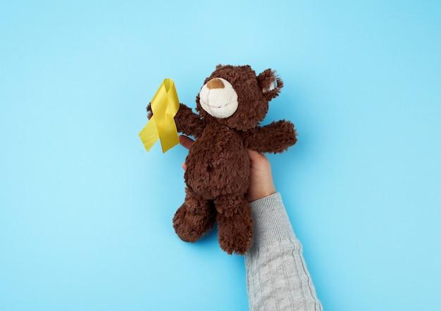 Kleine bruine teddybeer die in zijn poot een geel lint houdt dat in een lus is gevouwen
