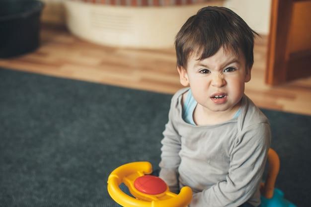 Kleine brunette jongen doet grappige gezichten tijdens het besturen van een plastic auto op de vloer in de woonkamer
