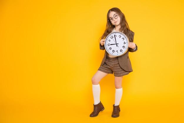 Kleine brunette meisje in kostuum met klokken