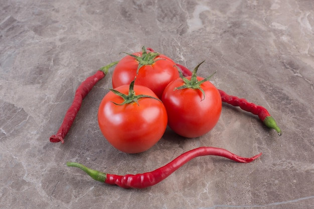 Kleine bundel tomaten omringd door drie paprika's op marmeren oppervlak