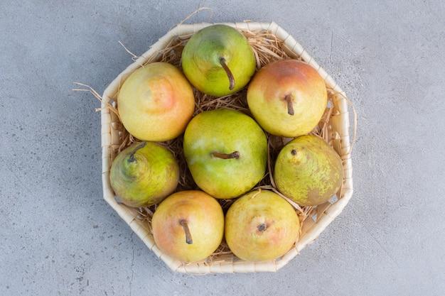 Kleine bundel van geassorteerde peren in een witte mand op marmeren achtergrond.