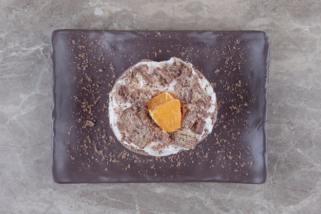 Kleine cake met gehakte oranje topping op een schaal op marmer