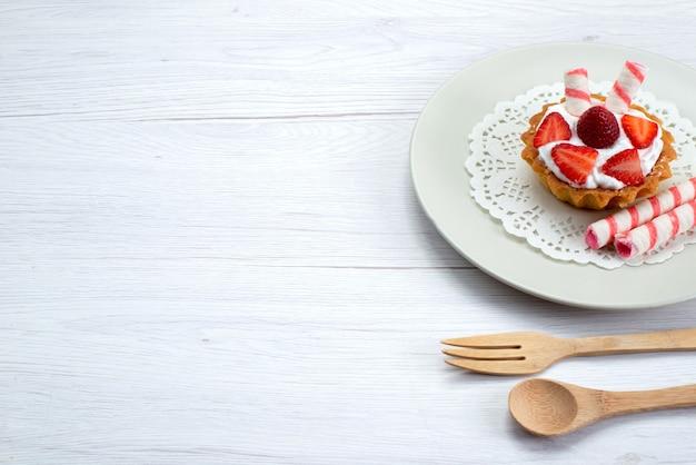 Kleine cake met room en gesneden aardbeien in plaat op wit bureau, fruitcake bessen zoete suiker