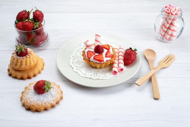 Kleine cake met room en gesneden aardbeien taarten snoepjes op wit, fruitcake bessen zoete suiker