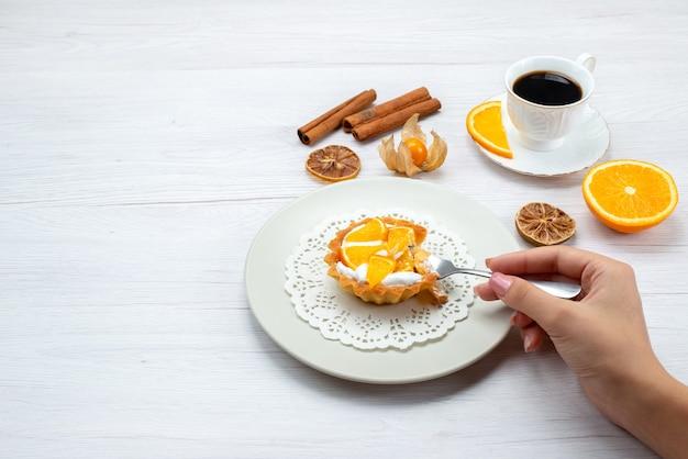 Kleine cake met room en gesneden sinaasappelen die door vrouw worden gegeten, samen met koffie en kaneel op licht bureau, fruitcake koekje zoete suiker