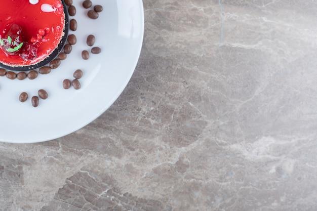 Kleine cake, met topping van aardbeiensiroop en koffiebonen op een schaal op marmeren ondergrond