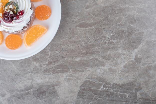 Kleine cake omringd met marmelade op een schaal op marmeren ondergrond
