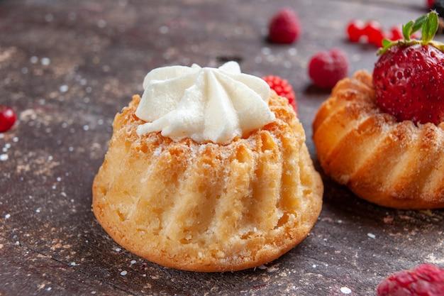 Kleine cakes met aardbeien en room op bruin, fruit bessen bakken cake koekje