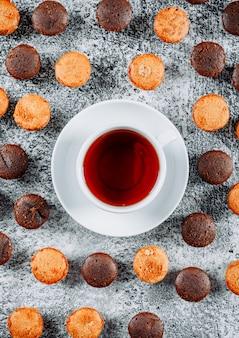 Kleine cakes met thee bovenaanzicht op een lichte structuur