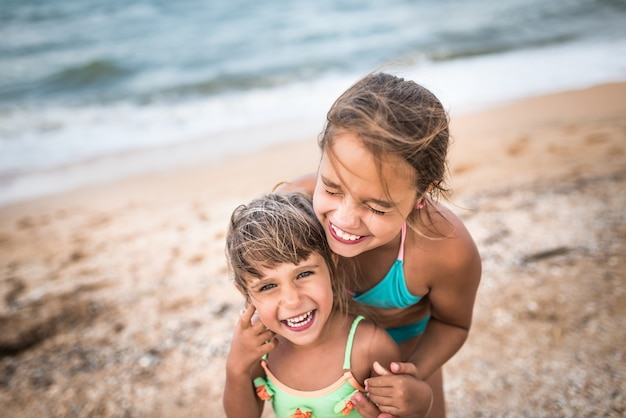 Kleine charmante zusjes fluisteren elkaar iets in het oor tijdens de zomervakantie op een warme zomerdag tegen een blauwe lucht