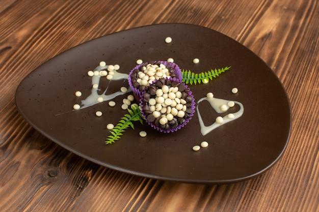 Kleine chocoladebrownies met chocoladeschilfers in donkere plaat op hout