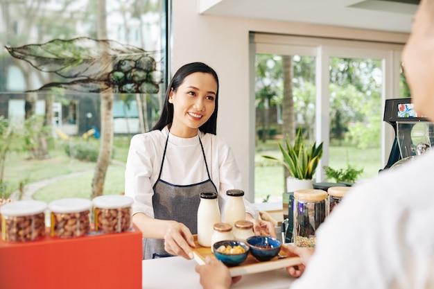 Kleine coffeeshop-serveerster die een dienblad met niet-zuivelyoghurt, melk en kommen cornflakes aan de klant geeft