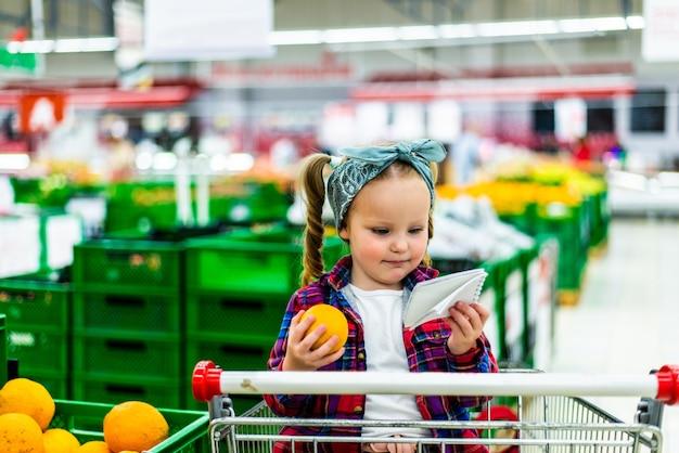 Kleine consument maakt lijst van producten om te kopen tijdens het winkelen in de supermarkt