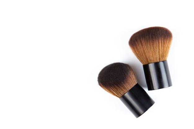 Kleine cosmetische make-upborstels die op witte achtergrond worden geïsoleerd