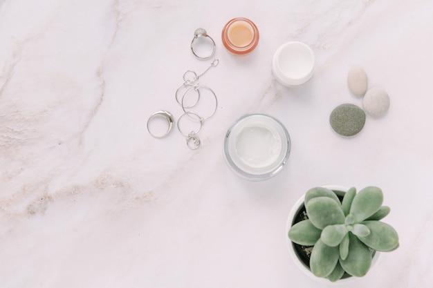 Kleine crèmeflessen met damesjuwelen, sappig in pot, schoonheid en spa-concept plat gelegd