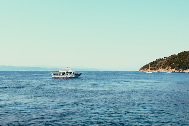 Kleine cruiseschepen op zee in de buurt van de griekse eilanden. kalme zee en blauwe hemelachtergrond. landschap van oranje berg met groene bomen op de ribben.