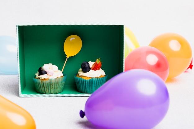 Kleine cupcakes in doos met luchtballons