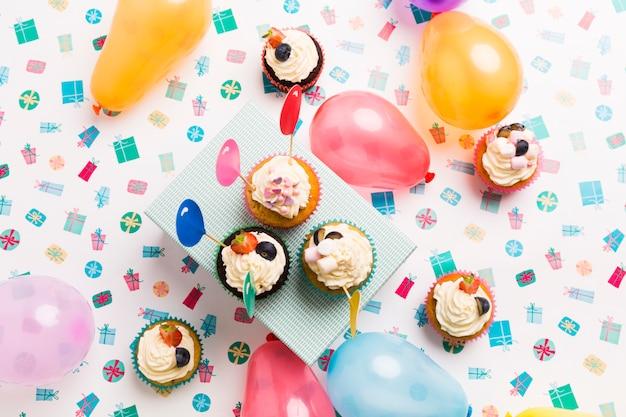Kleine cupcakes met ballonnen op tafel