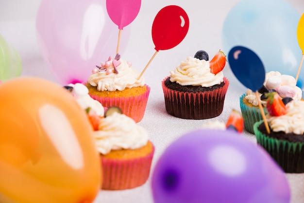 Kleine cupcakes met luchtballons op lichte lijst