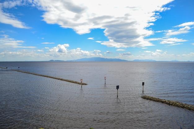 Kleine dammen in de zee en de blauwe lucht, witte wolken.