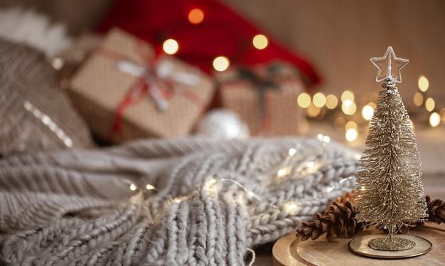 Kleine decoratieve glanzende kerstboom op de voorgrond op een onscherpe achtergrond van een gebreide sjaal, kerstversiering en bokeh lichten kopiëren ruimte.