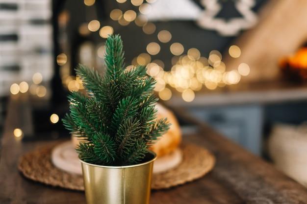Kleine decoratieve kerstboom in een pot in de keukentafel.